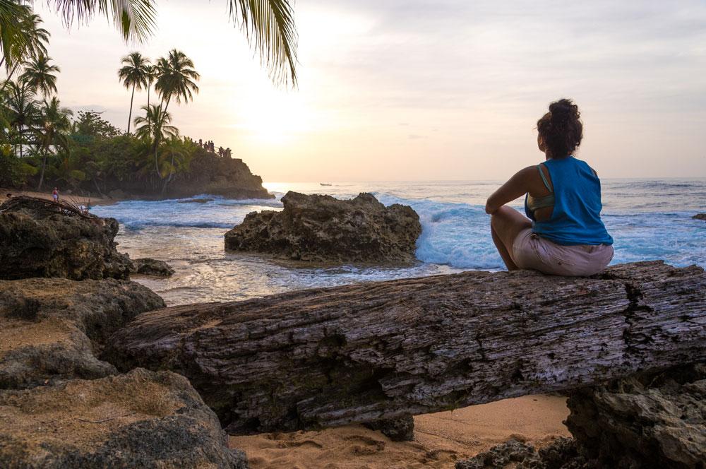 lady sitting by costa rican beach on a log yoga retreat article